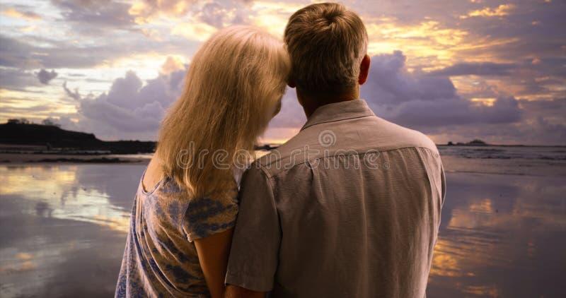 在观看日落的爱的愉快的资深夫妇在海滩 免版税库存图片