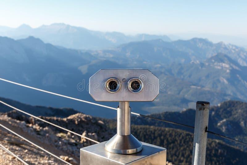 在观看的平台的公开双筒望远镜反对在山的背景美好的风景 库存照片