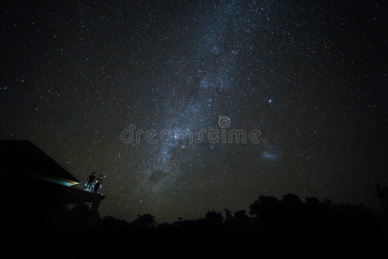在观看mliky方式和星在夜空的屋顶的夫妇在巴厘岛 库存图片