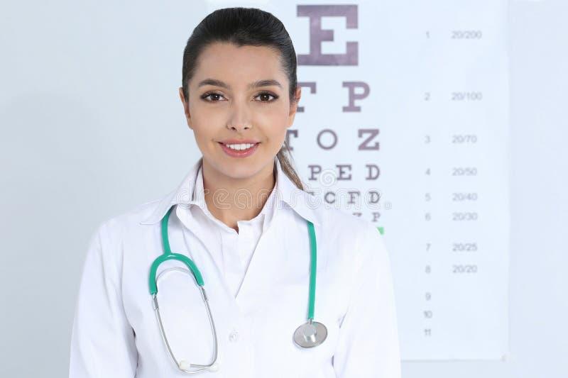在视力检查表附近的女孩的医生 图库摄影