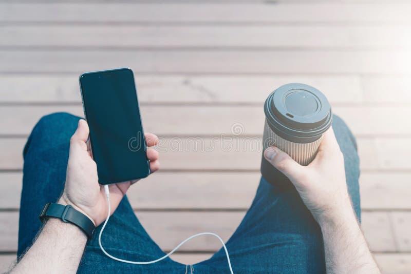 在视图之上 从眼睛的看法 智能手机特写镜头有黑黑屏和咖啡的在行家的手上 库存照片