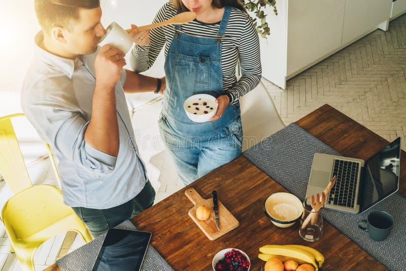 在视图之上 年轻夫妇在烹调早餐人的厨房是常设近的桌和饮用的茶 免版税图库摄影