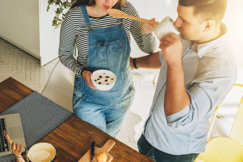 在视图之上 年轻夫妇在烹调早餐人的厨房是常设近的桌和饮用的茶 库存图片