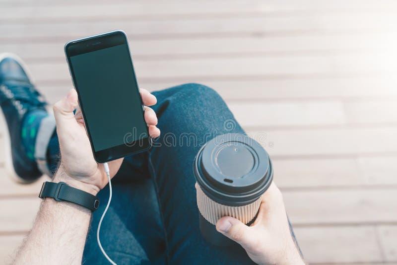 在视图之上 智能手机特写镜头有黑屏的和咖啡在行家的手上供以人员坐 免版税库存照片