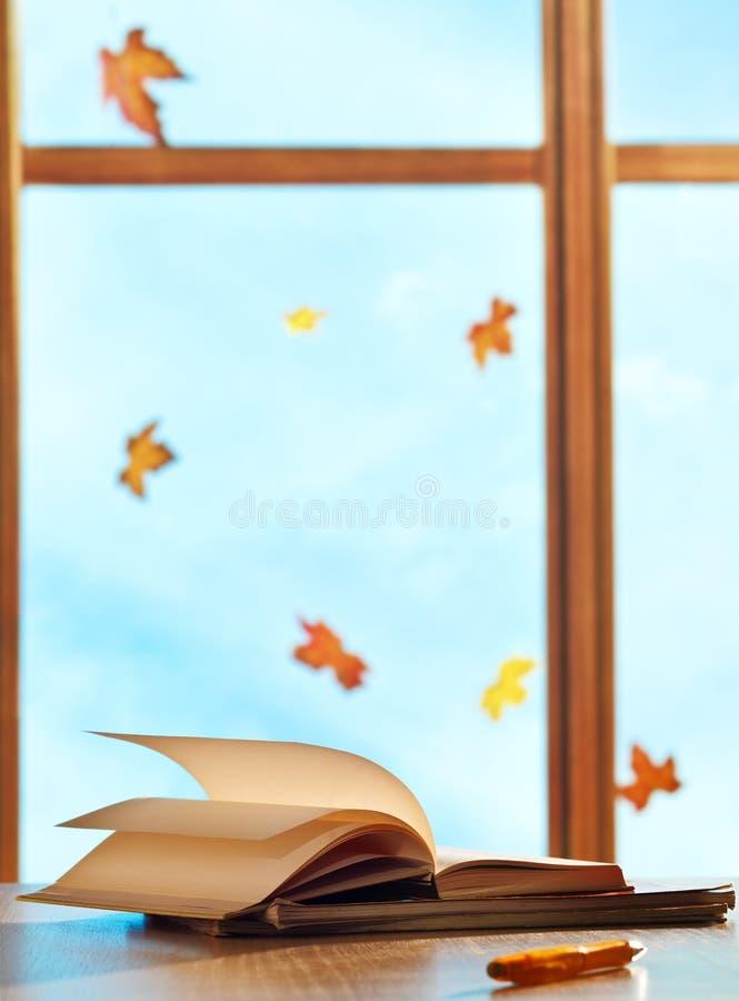 在视窗背景的课本与槭树叶子 库存图片