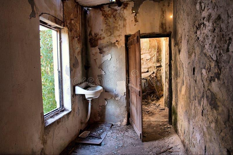 在视窗里面的被放弃的门房子 免版税图库摄影
