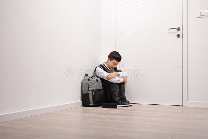 在角落安装的哀伤的少年学生 免版税库存照片