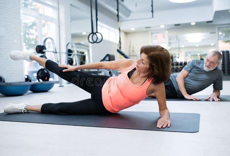 在解决的健身房的资深夫妇,举的腿 免版税库存照片