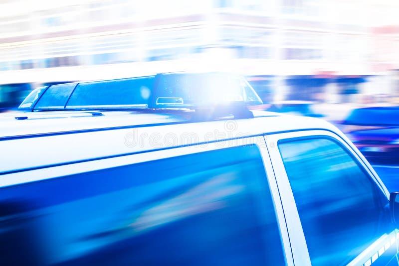 在警车的闪动的蓝色光 免版税库存图片