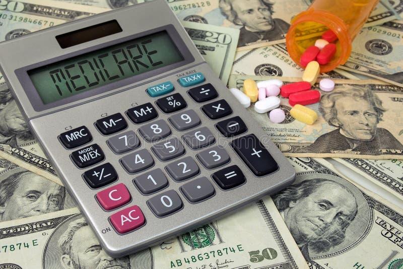 在计算器的医疗保障文本有金钱和药片的 库存照片