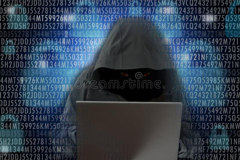 """在计算机â€前面的无法认出的黑客""""网络罪行概念 图库摄影"""