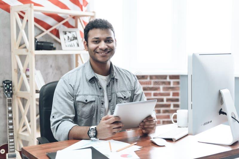 在计算机上的印地安年轻商人工作在表上 免版税库存照片