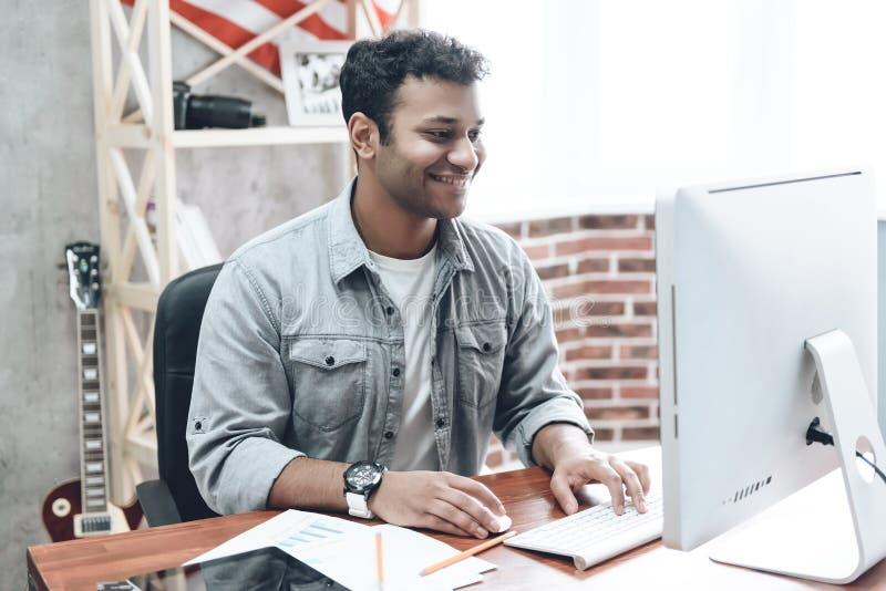 在计算机上的印地安年轻商人工作在表上 库存图片