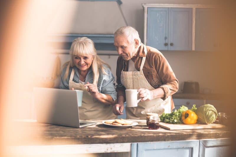 在计算机上的激动的成熟夫妇读书食谱 免版税库存照片