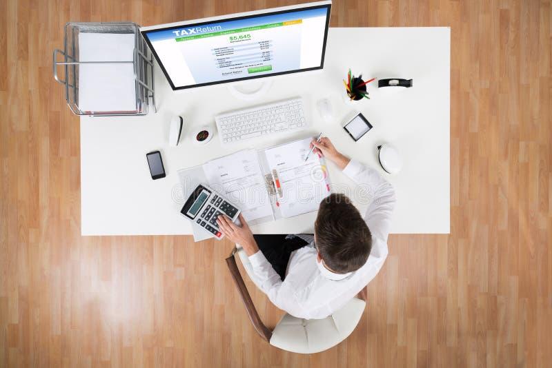 在计算机前面的商人计算的税 免版税库存图片
