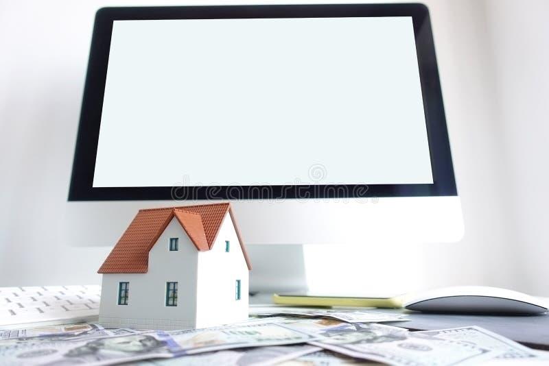 在计算机前面的式样房子有作为背景的空的白色屏幕的,站立在现金钞票 房地产网上transac 免版税库存照片