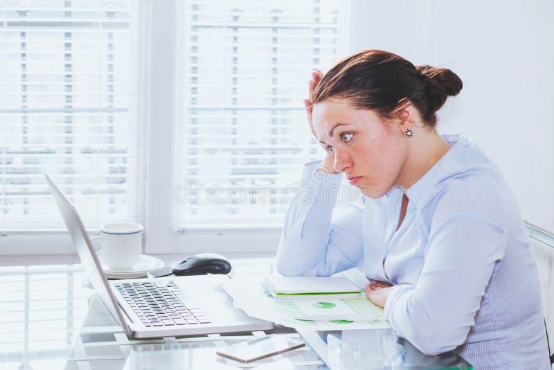 在计算机前面的恼怒的愤怒的妇女 库存照片