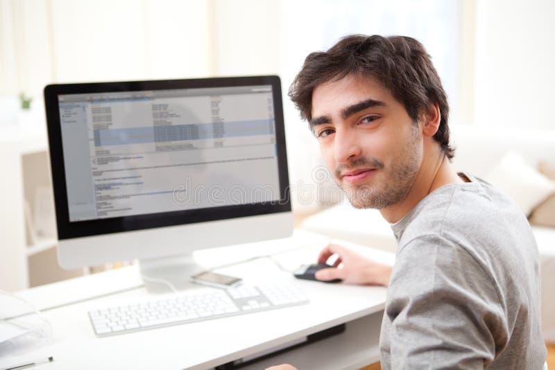 在计算机前面的年轻微笑的人 库存图片