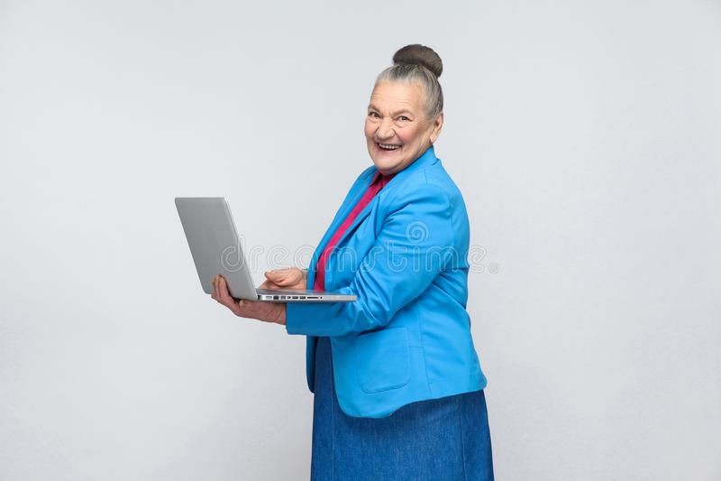 在计算机和暴牙微笑的年迈的妇女工作 图库摄影