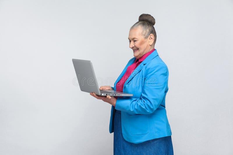 在计算机的年迈的妇女工作 免版税库存图片