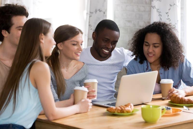 在计算机的微笑的不同的人民观看的喜剧电影 免版税库存照片
