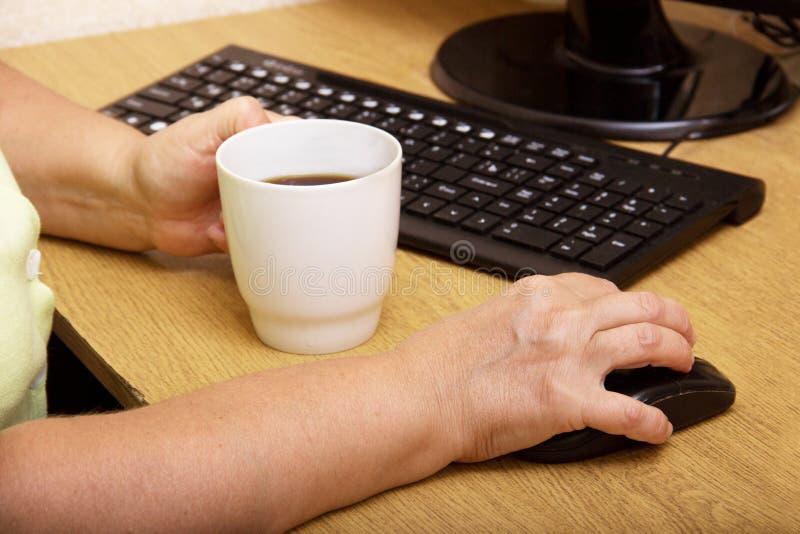 在计算机老鼠的一只年长妇女手 老祖母在键盘后工作并且喝咖啡 免版税库存照片