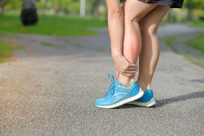 在训练期间,举行他的体育腿伤,干涉痛苦 图库摄影