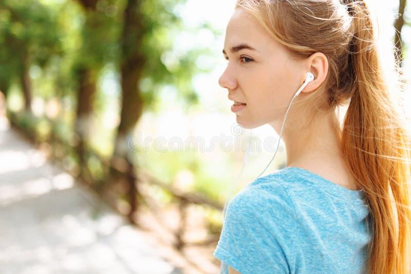 在训练期间,女孩听到在耳机的音乐,跑在新鲜空气,早晨训练 图库摄影