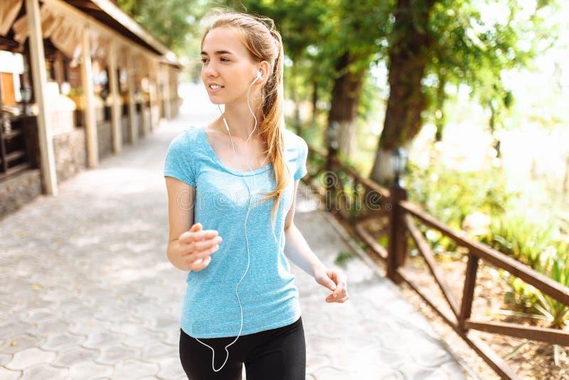 在训练期间,女孩听到在耳机的音乐,跑在新鲜空气,早晨训练 免版税图库摄影