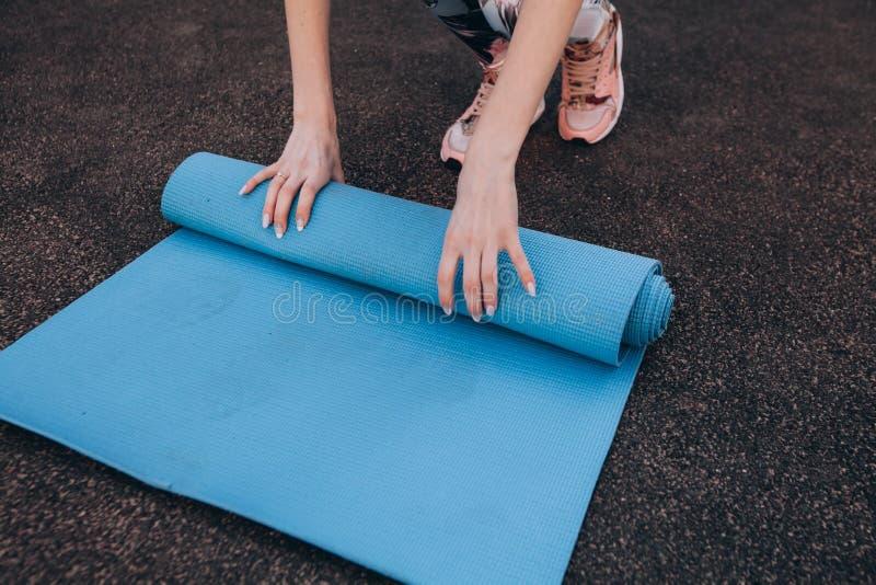 在训练的蓝色健身席子在体育场以后 免版税库存照片
