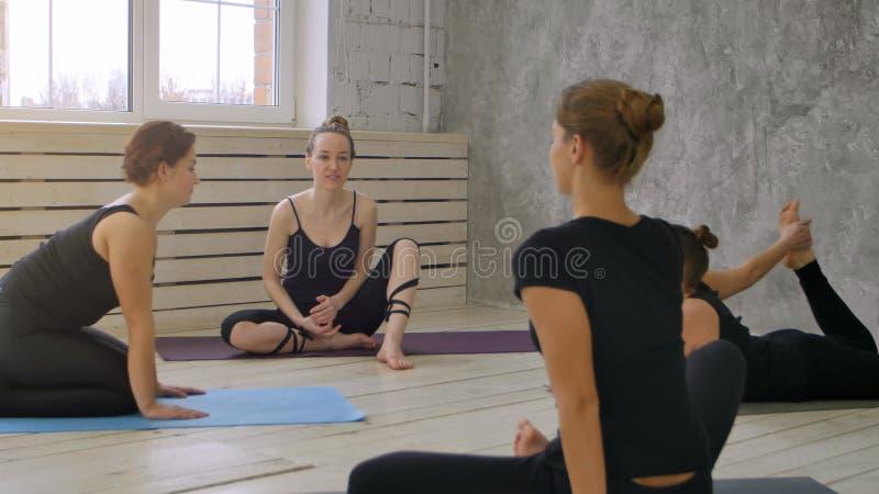 在训练谈话和舒展编组微笑的妇女在瑜伽类前 免版税库存图片