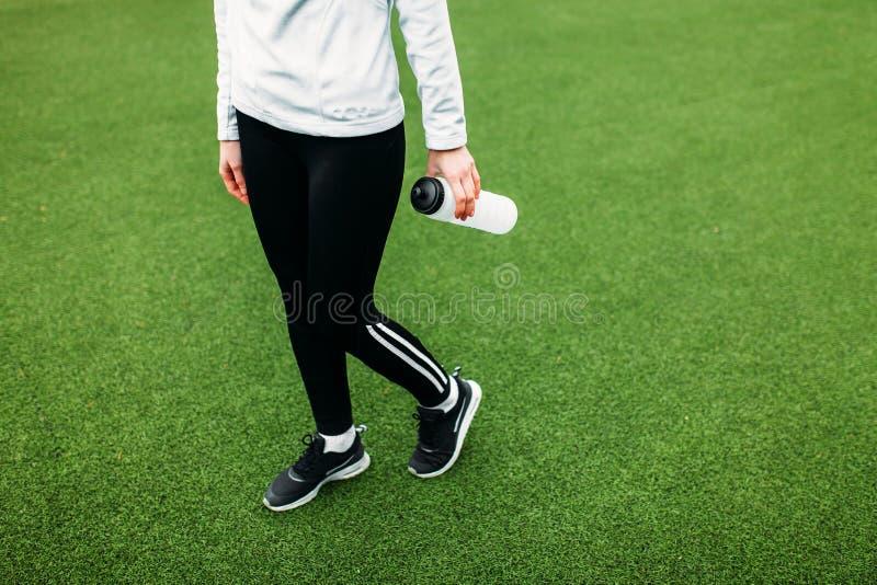 在训练,跑或者体育以后的女孩在前景,一个瓶的休息水 女孩在开放,新鲜空气工作 库存图片