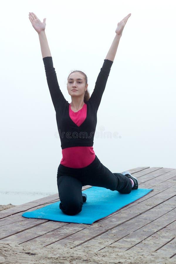 在训练w期间,做舒展的年轻健身妇女行使 免版税图库摄影
