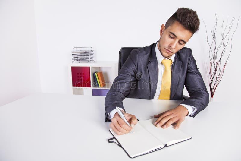 在记事本的生意人文字 免版税图库摄影
