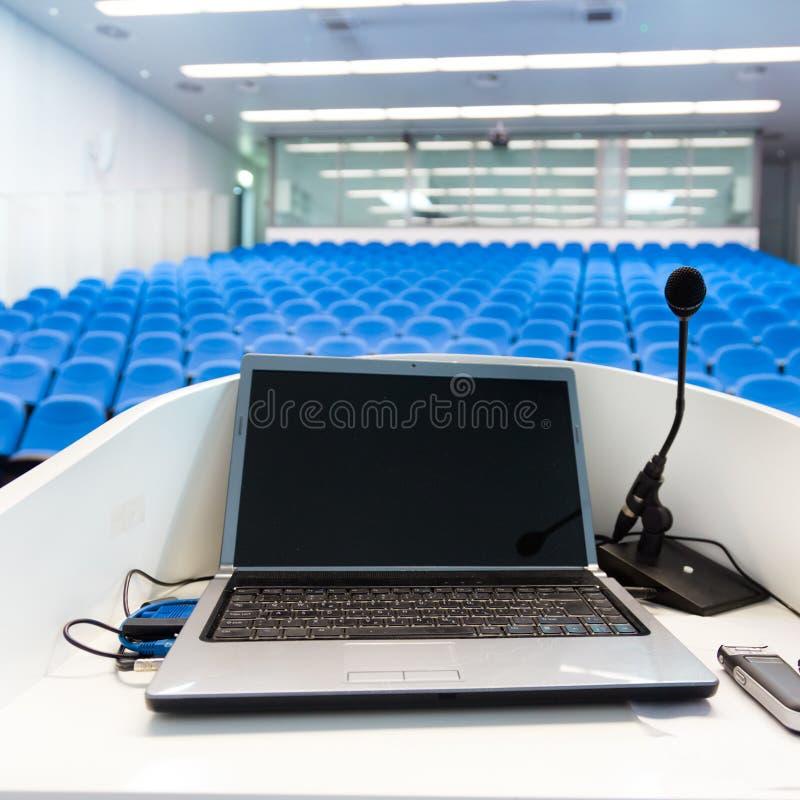 在讲台的膝上型计算机在会场里。 免版税库存照片