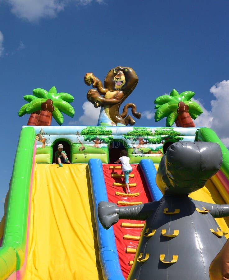 在许多庆祝的儿童inflatables在城市的那天 图库摄影
