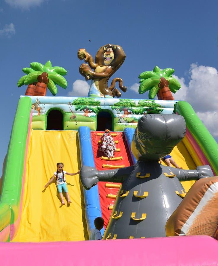 在许多庆祝的儿童inflatables在城市的那天 免版税图库摄影