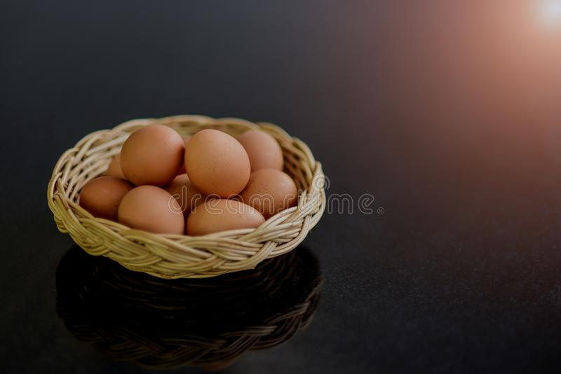 在许多柳条筐的新鲜的鸡蛋在作为原料准备的一张黑石桌上为烹调 免版税库存图片