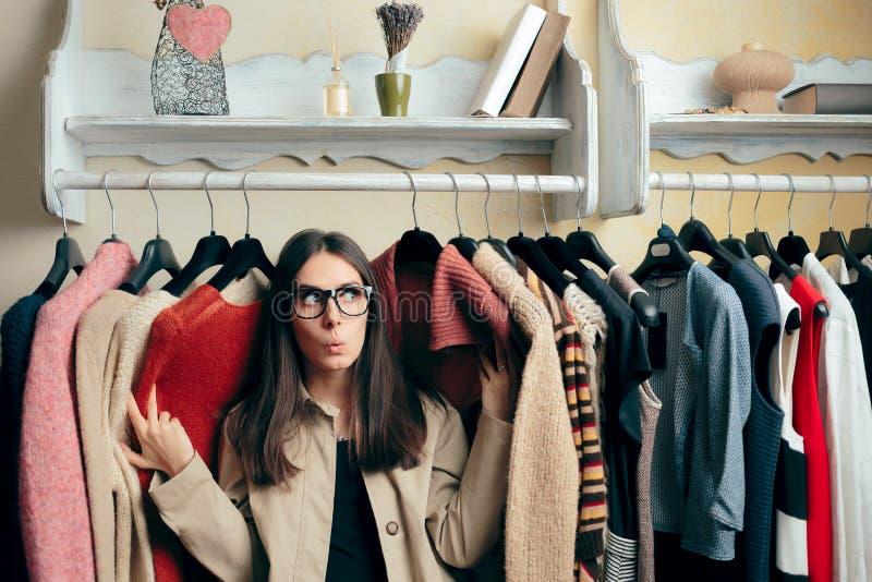 在许多毛线衣之间的滑稽的女孩在衣物Stander 免版税图库摄影