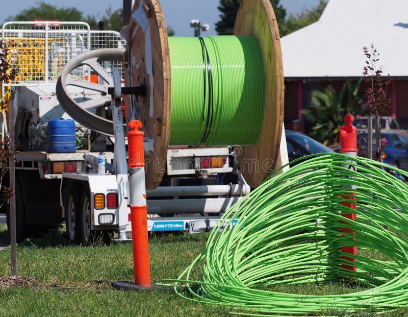 在设施卡车后的绿色光纤NBN缆绳 免版税库存图片