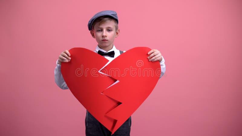 在设法葡萄酒的穿戴的哀伤的男性孩子修理残破的纸心脏,单相思 库存图片