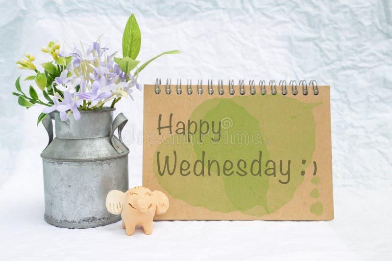 在设计笔记本盖子的愉快的星期三有微笑的大象黏土玩偶和花盆的 库存照片