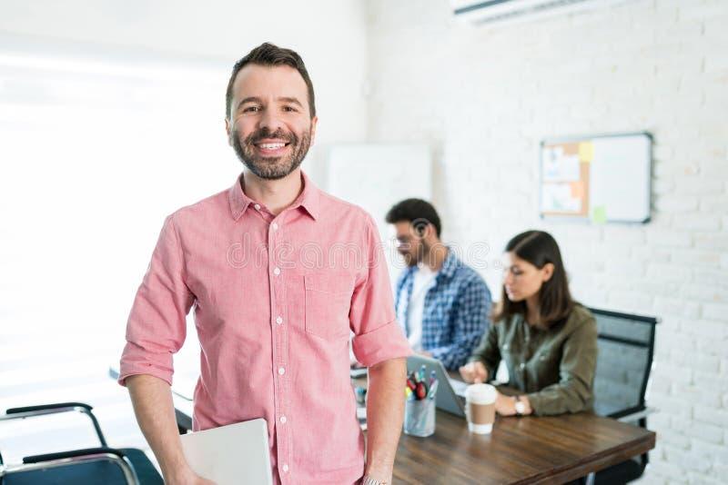 在证券交易经纪人行情室的愉快的商人在办公室 免版税库存图片