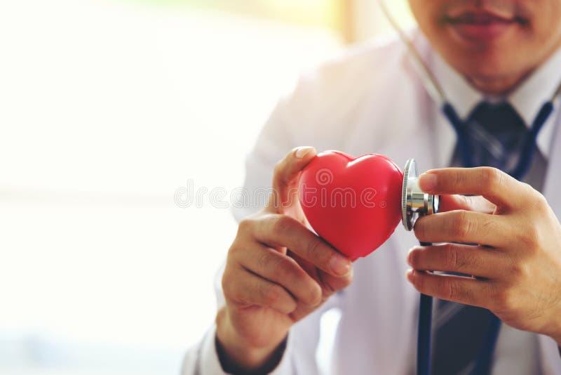 在诊所办公室,健康锂篡改握有红色心脏的手 免版税图库摄影
