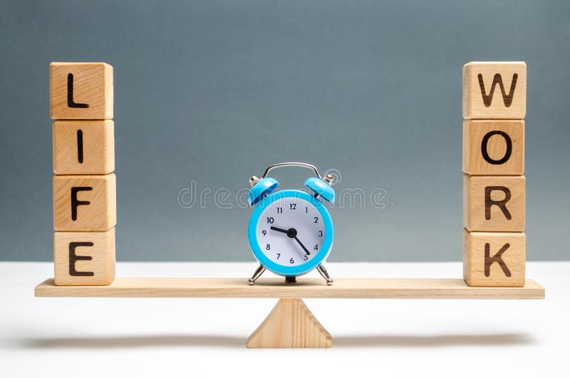 在词生活和工作之间的蓝色时钟在等级 在生活和工作之间的选择 注意的概念 库存照片
