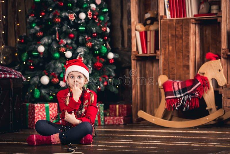 在诗歌选和展示猪鼻子包裹的圣诞老人女孩 免版税库存照片