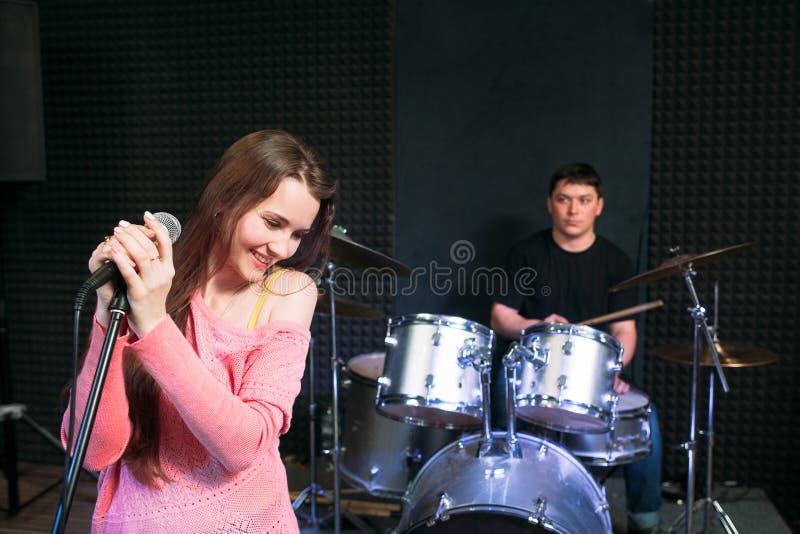 在话筒附近的害羞的女歌手在场面 免版税库存照片