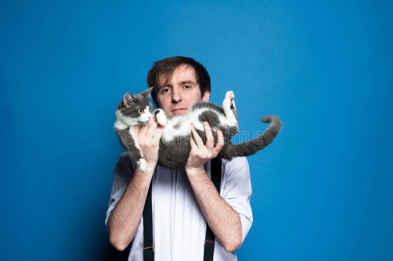 在说谎在后面逗人喜爱的灰色和白色猫和看在蓝色背景前面的面孔附近的人藏品照相机 免版税库存图片