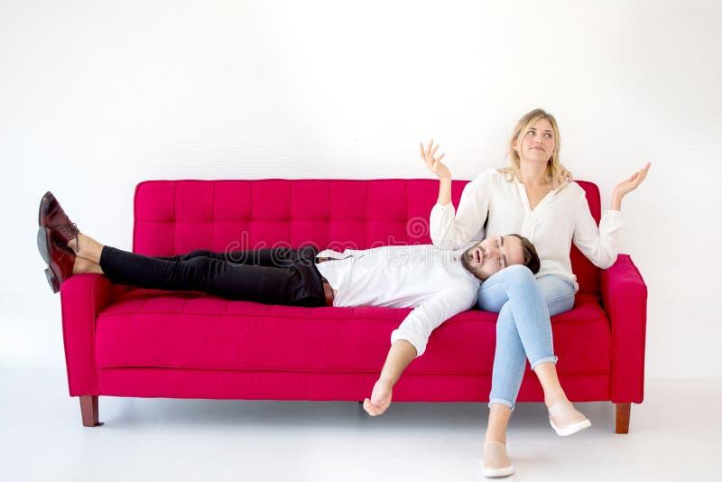 在说谎在或睡眠红色沙发的在家下的爱男朋友的在她的膝盖或腿女朋友的夫妇在白色背景,户内 免版税库存图片