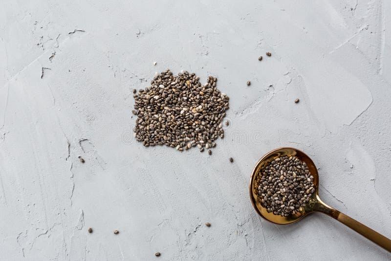 在说谎在灰色具体背景的匙子的Chia种子 r 重量的饮食 E 平的位置,大模型 图库摄影